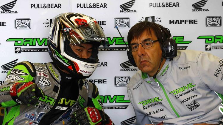 Honda MotoGP rider Aoyama of Japan speaks to a team member during a practice session for the British Grand Prix at the Silverstone Race Circuit