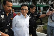 Abdul Razak Baginda (C), a high-profile political analyst, walks towards the court room in police custody in Shah Alam, west of Kuala Lumpur, in 2008. A scandal linking Malaysia&#39;s leader, a young woman&#39;s murder and alleged kickbacks in a French submarine deal has resurfaced as a potential danger for the government as elections loom