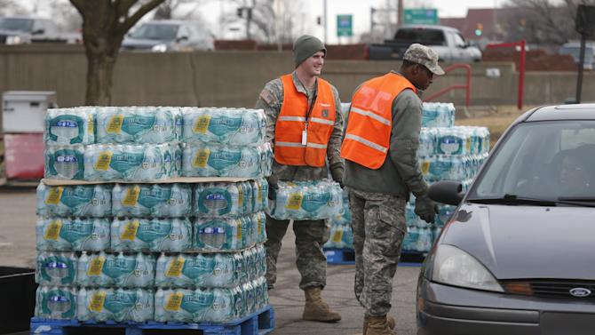 Michigan National Guardsmen distribute bottled water to Flint residents at a fire station in Flint