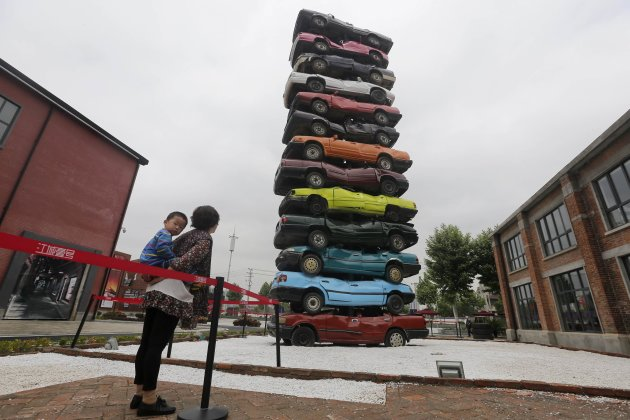 People look at a sculpture made of 13 scrapped cars of various colours created by Gu and Sun at a cultural industrial park in Wuhan