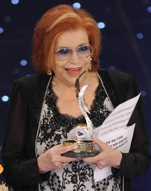 "FILE - In this Feb. 18, 2010 file photo Nilla Pizzi is honored with a prize for her career during the ""Festival di Sanremo"" Italian song contest at the Ariston theater in San Remo, Italy. Nilla Pizzi, winner of the first San Remo festival, and whose voice was deemed too sensual to sing on radio during the fascist regime of Benito Mussolini, died on Saturday. She was 91, said RAI state TV, which broadcasts the week-long festival of Italian song each year. The Italian President Giorgio Napolitano in a condolence message hailed Pizza as a ""sensitive and popular interpreter of the Italian melodic tradition."" During fascist rule in the years before World War II, Pizzi was kept away from radio work because her voice was deemed too ""modern, exotic and sensual,"" the Italian news agency said. (AP Photo/Alberto Pellaschiar, File)"