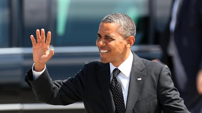 President Barack Obama waves upon his arrival, Tuesday, July 24, 2012, at the 142nd Fighter Wing Oregon Air National Guard Base, in Portland, Ore. President Barack Obama has arrived in Oregon to raise money for his re-election campaign.  (AP Photo/Rick Bowmer)