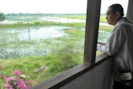 A visitor is seen looking out from the former Khmer Rouge commander Ta Mok's house at Anlong Veng district in Oddar Mean Chey province, some 400 km northwest of Phnom Penh. Anlong Veng, near the Thai border, was the Khmer Rouge's last rebel centre before the movement disintegrated in the late 1990s