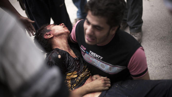 FILE - In this Thursday, Oct. 11, 2012 file photo, a Syrian man cries while holding the body of his brother, killed by Syrian Army shelling, near Dar al-Shifa hospital in Aleppo, Syria. The Aleppo rebellion started off in the rural areas of Aleppo province, not in the city as was the case in most other parts of Syria. Regime forces punish the city daily with artillery and airstrikes. Civilians are killed and wounded while standing on breadlines, walking the streets or watching television at home. Snipers target civilians in areas where rebels have positions. Members of staff at the rebels' field hospital say 80 percent of the average 100-120 cases they treat daily are civilians. Some residents blame the rebels. (AP Photo/Manu Brabo, File)