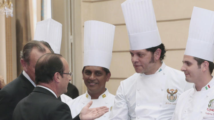 "French President Francois Hollande, left, shakes hand with Hilton Little, 2nd right, chef at the South African president residence during a reception at the Elysee palace in Paris, Tuesday July 24, 2012, following the ""Chef des Chefs Club"" (CCC) international meeting. (AP Photo/Jacques Demarthon, Pool)"