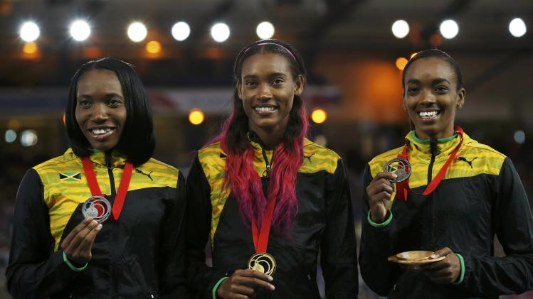 Mcpherson of Jamaica holds her gold medal beside compatriots Williams-Mills and Day, after the Women's 400m final at the Commonwealth Games in Glasgow