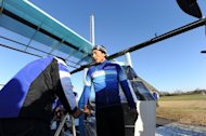 "Japanese professional cyclist Kazuhiro Yamamoto exits the cockpit of a man-powered airplane ""Gokuraku-tonbo"" (Happy-go-lucky), produced by Yamaha Motor engineers belonging to ""Team Aeroscepsy"" at the Honda airport in suburban Tokyo on December 2. The team hopes to beat the world record for a human-propelled plane"