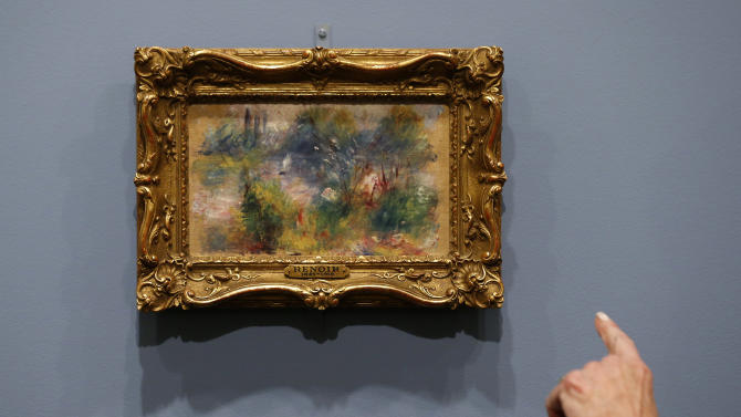 """A woman points at details in Pierre-Auguste Renoir's painting """"On the Shore of the Seine"""" after a news conference at the Baltimore Museum of Art in Baltimore, Thursday, March 27, 2014, more than 60 years after it was stolen from the museum. The painting became the subject of a dramatic legal dispute after a Virginia woman claimed she bought it at a flea market for $7. A judge ultimately awarded ownership back to the Baltimore museum, and it is scheduled to go on public display March 30. (AP Photo/Patrick Semansky)"""