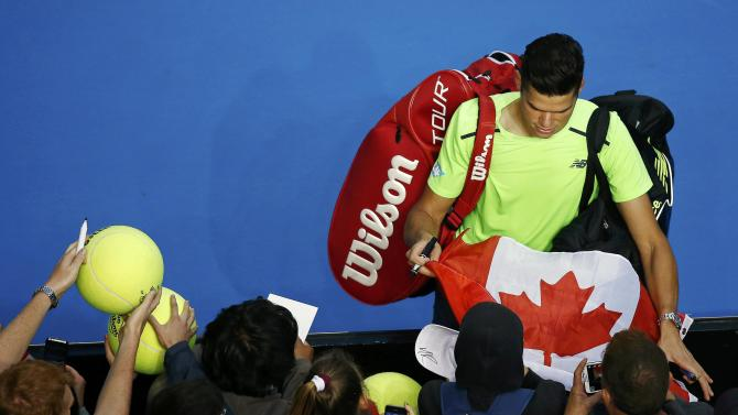 Raonic of Canada signs autographs after defeating Lopez of Spain in their men's singles match at the Australian Open 2015 tennis tournament in Melbourne