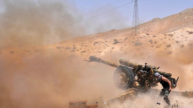 A Syrian soldier fires artillery shells towards Islamic State (IS) group jihadists during clashes near the northeastern city of Palmyra, on May 17, 2015
