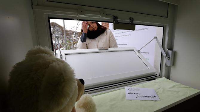 """Galina Murzakayeva, a coordinator for Kolybel Nadezhdy (Cradle of Hope), a non-governmental organization, opens the baby box in Kirishi, an industrial town of 50,000 located 100 kilometers (60 miles) east of St. Petersburg, Russia, Wednesday, Oct. 31, 2012. A box in which parents can leave their babies anonymously and without any legal risk opened Wednesday in the town of Kirishi in northwestern Russia, in part of an effort activists hope will save many young lives. The box in Kirishi is the tenth such facility in Russia, just a fraction of what experts think is needed to help save hundreds of babies abandoned by their mothers each year. The sign reads """"A letter to parents."""" (AP Photo/Dmitry Lovetsky)"""