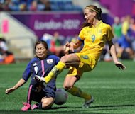 Sweden's midfielder Kosovare Asllani (R) fights for the ball with Japan's midfielder Nahomi Kawasumi during their London 2012 Olympic women's football match at The City of Coventry Stadium in Coventry, central England