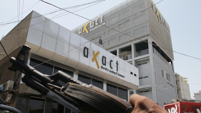 A Pakistani police officer stands guard at the office of Axact software company in Karachi, Pakistan, Wednesday, May 27, 2015. Pakistani authorities on Wednesday detained the owner of a software company accused of running a global network in selling fake degrees, officials said. (AP Photo/Fareed Khan)