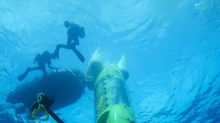 This February 2012 handout photo provided by National Geographic shows the DEEPSEA CHALLENGER submersible beginning its first test dive off the coast of Papua New Guinea. Earth's lost frontier, the deepest part of the oceans where the pressure is like three SUVs sitting on your little toe, is about to be explored first-hand. It's been more than half a century since man dared to plunge that deep. Earth's lost frontier is about to be explored firsthand after more than half a century.  (AP Photo/Mark Thiessen, National Geographic)