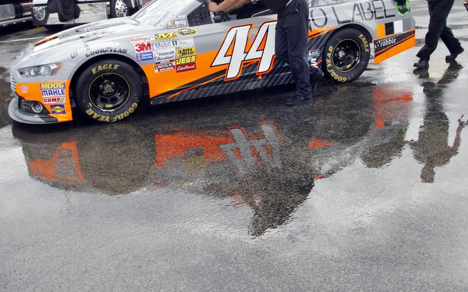 Crew members for Scott Riggs push his car through puddles between stations during tech inspection for the NASCAR Sprint Cup auto race at Kentucky Speedway in Sparta, Ky., Saturday, June 29, 2013. (AP Photo/James Crisp)