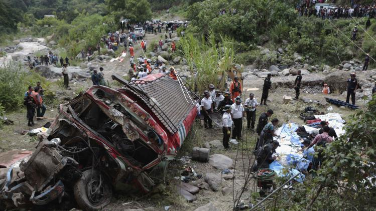 Forensic technicians work at a bus crash site in San Martin Jilotepeque, Chimaltenango region