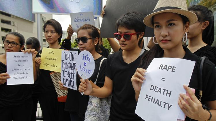 Thai social media users hold banners during a rally calling for the death penalty for rapists, outside a shopping mall in Bangkok