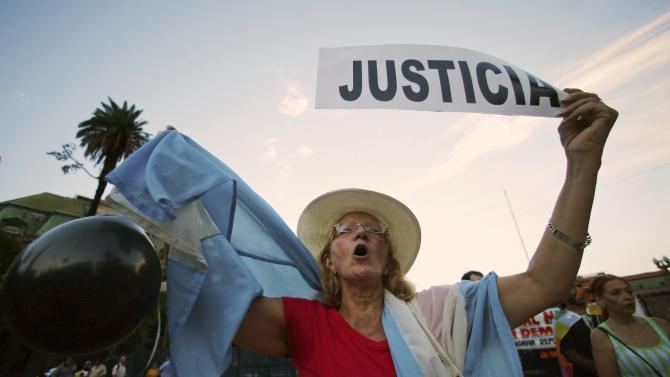 A woman holds up a sign during a demontration to demand justice over the death of Nisman in Buenos Aires