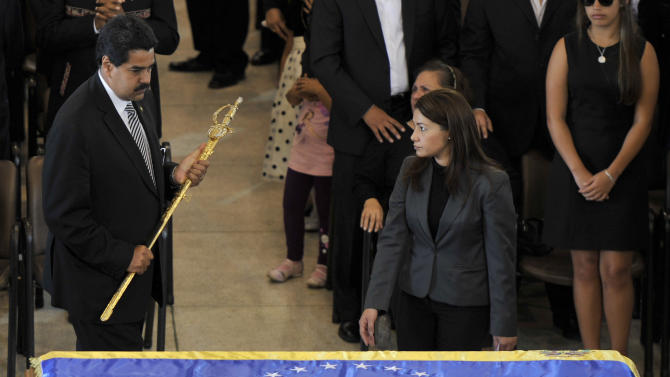 In this image released by the office of Mexico's Presidencia, Venezuela's Vice President Nicolas Maduro, left, holds a replica of Simon Bolivar's sword next to the flag-draped coffin of Venezuela's late President Hugo Chavez during the funeral ceremony at the military academy in Caracas, Venezuela, Friday, March 8, 2013. Chavez died on March 5 after a nearly two-year bout with cancer. (AP Photo/Presidencia de la Republica de Mexico, Daniel Aguilar)