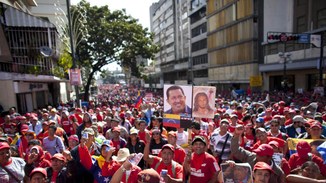 Supporters  of Venezuela's President Hugo Chavez chants slogans during a rally in Caracas, Venezuela, Thursday, Jan. 10, 2013. Hundreds of cheerful supporters rallied outside his presidential palace Thursday in an alternative inauguration for a leader too ill to return home for the real thing. (AP Photo/Ariana Cubillos)