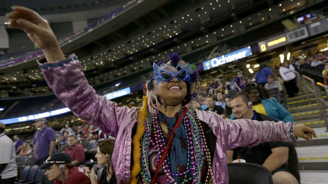Jennifer Jones, of New Orleans, wearing Mardi Gras attire dances in the isles of the Superdome during media day for the NFL Super Bowl XLVII football game Tuesday, Jan. 29, 2013, in New Orleans. (AP Photo/Gerald Herbert)