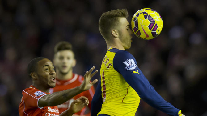Arsenal's Calum Chambers, right, fights for the ball against Liverpool's Raheem Sterling during the English Premier League soccer match between Liverpool and Arsenal at Anfield Stadium, Liverpool, England, Sunday Dec. 21, 2014. (AP Photo/Jon Super)