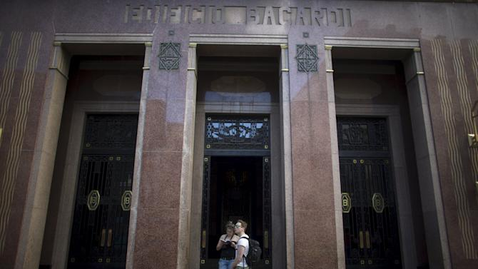Tourists stand at the entrance of the former headquarters of Bacardi in Havana