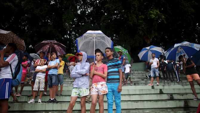Boys protect themselves from the rain as they watch the friendly match between New York Cosmos and Cuba's national team in Havana