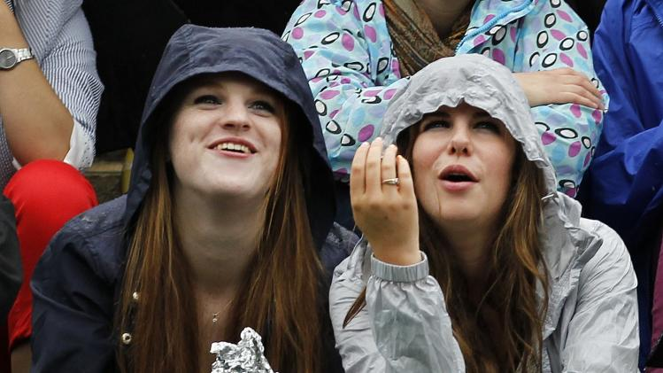 Spectators gathered on 'Murray Mount' react as they watch on a big screen Andy Murray of Britain playTommy Robredo of Spain in a Men's singles match at the All England Lawn Tennis Championships in Wimbledon, London, Friday, June 28, 2013. (AP Photo/Sang Tan)