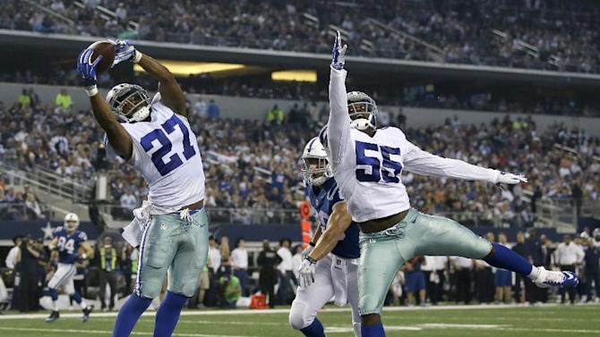 Dallas Cowboys free safety J.J. Wilcox (27) reaches up to intercept a pass intended for Indianapolis Colts tight end Coby Fleener, rear, as Rolando McClain (55) watches during the first half of an NFL football game, Sunday, Dec. 21, 2014, in Arlington, Texas. (AP Photo/Tim Sharp)