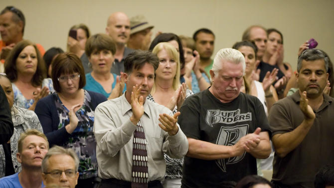 A standing room only council chambers gives Ron Thomas, father of Kelly Thomas, a standing ovation after her spoke before the Fullerton city council on Tuesday night Aug. 2, 2011. (AP Photo/Leonard Ortiz - Orange County Register)