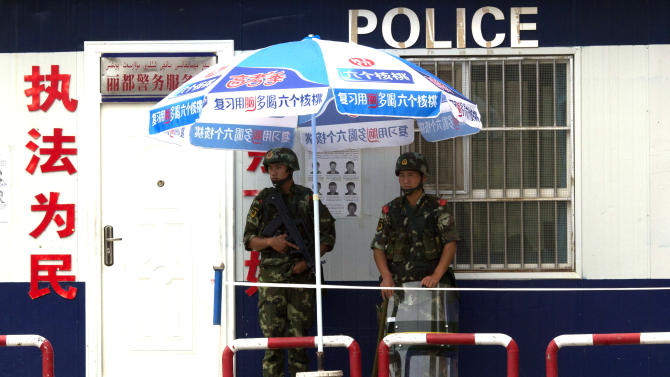 In this July 17, 2014 photo, armed Chinese paramilitary policemen stand on duty near wanted posters at a check point in Aksu in western China's Xinjiang province. The Chinese government uses expansive controls and propaganda to maintain a virtual monopoly on the narrative in the tense region of Xinjiang, where minority Uighurs complain of oppression under Beijing's rule. (AP Photo/Ng Han Guan)