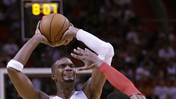 Miami Heat forward Chris Bosh (1) looks for an open teammate past Houston Rockets forward Terrence Jones (6) during the first half of a preseason NBA basketball game, Tuesday, Oct. 21, 2014 in Miami. The Heat defeated the Rockets 90-85. (AP Photo/Wilfredo Lee)
