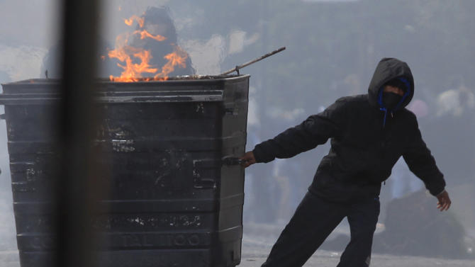 FILE - In this Monday Aug. 8, 2011 file photo a masked youth pulls a burning garbage bin set on fire by rioters in Hackney, east London.   More than two weeks after the end of riots in London and other English cities, Britain's government and police met social media executives Thursday to discuss how to prevent their services from being used to plot violence. (AP Photo/Lefteris Pitarakis, File)