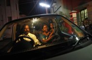 R. Umamangeshwari, a 42-year-old housewife, holds her adopted daughter Janani (R), a cradle baby, as her husband drives a car outside the Life Line Trust orphanage in Salem in the southern Indian state of Tamil Nadu June 20, 2013. Thomson Reuters Foundation/Mansi Thapliyal