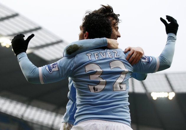 Manchester City's Carlos Tevez, foreground, reacts with teammate David Silva after scoring a goal against Notts County during their FA Cup fourth round replay soccer match at the City of Manchester St