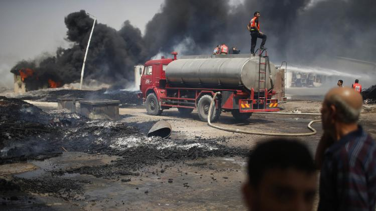 Palestinian fire-fighters try to extinguish a fire which police said was caused by an Israeli tank shelling in the industrial area in the east of Gaza City