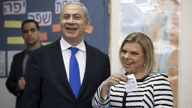 FILE - In this Tuesday, Jan. 22, 2013 file photo, Israeli Prime Minister Benjamin Netanyahu stands by his wife Sara as she casts her ballot at a polling station in Jerusalem. As his government is slashing welfare benefits and hiking takes for the working class to overcome a huge deficit, Israeli Prime Minister Benjamin Netanyahu is finding himself under fire again for his lavish lifestyle. (AP Photo/Uriel Sinai, File)