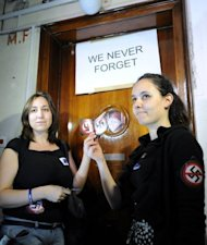 Activists from the European Union of Jewish Students hold up &#39;No Nazi&#39; symbols in front of Laszlo Csatary&#39;s hideaway building, only a few kilometers from his home in Budapest. Hungarian authorities detained, grilled and put under house arrest Csatary, age 97
