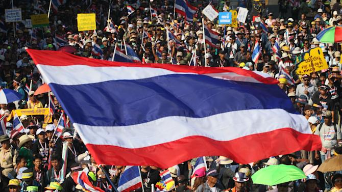 Anti-government protesters with national flags gather for a rally Monday, Jan. 13, 2014, in Bangkok, Thailand. Anti-government protesters took over key intersections in Thailand's capital Monday, halting much of the traffic into Bangkok's central business district as part of a months-long campaign to thwart elections and overthrow the democratically elected prime minister.(AP Photo/Sakchai Lalit)