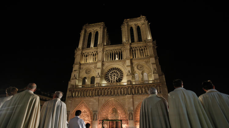 Religious dignitaries stand in front of Paris' Notre Dame Cathedral as part of a ceremony for its 850th anniversary, Wednesday, Dec. 12, 2012. Dignitaries, tourists and Parisians gathered in the thousands for a ceremony and Mass marking the beginning of year-long commemoration of Notre Dame Cathedral's 850th anniversary. (AP Photo/Christophe Ena)