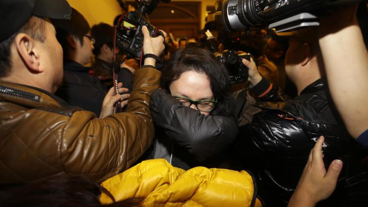 A relative of a passenger of Malaysia Airlines flight MH370 covers her face as she walks past journalists at a hotel in Beijing