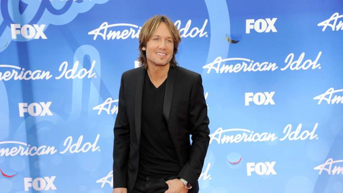 """FILE - This May 16, 2013 file photo shows Keith Urban at the """"American Idol"""" finale in Los Angeles. Urban will return as a judge on the singing competition series. (Photo by Chris Pizzello/Invision/AP, File)"""