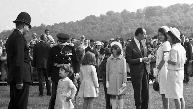 FILE - In this May 14, 1965 file photo, John Kennedy Jr., son of U.S. President John F. Kennedy, talks with a British police officer after the dedication ceremony for the memorial to the late president at Runnymede, Surrey, England. At second right is Jacqueline Kennedy. On an English hillside near where the Magna Carta was signed eight centuries ago, a seven ton Portland stone memorial stands on the historic grounds on an acre of land which became American property, in perpetuity - a gift from the British people. (AP Photo/File)