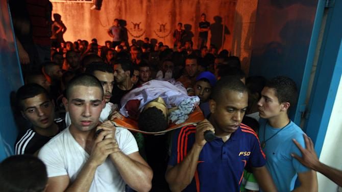 Palestinians carry the body of Yosuf abu Zaghah, 20, who was killed by the Israeli troops in the West Bank refugee camp of Jenin Early on Tuesday, July 1, 2014. Abu Zaghah, a Palestinian from the militant group Hamas was shot dead when he threw a grenade at forces carrying out an arrest raid in the West Bank hours after the discovery of the bodies of three Israeli teenagers who were abducted over two weeks ago, Israel's military said Tuesday. (AP Photo/Mohammed Ballas)