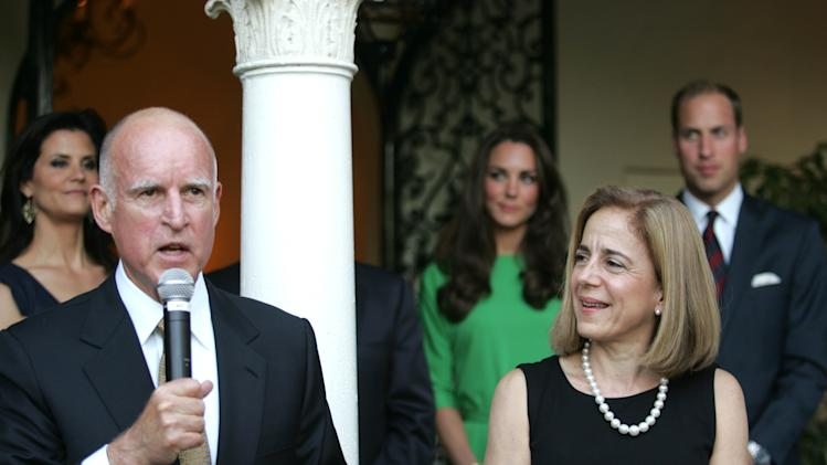 California Gov. Jerry Brown, speaks as his wife Anne Gust Brown looks on during a reception honoring Prince William and Kate, the Duke and Duchess of Cambridge, background right, at the Hancock Park home of the British Consulate General in Los Angeles, on Friday, July 8, 2011.  (AP Photo/Matt Baron, pool)