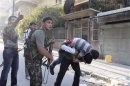 A member of the Free Syrian Army carries his wounded comrade during clashes in Aleppo