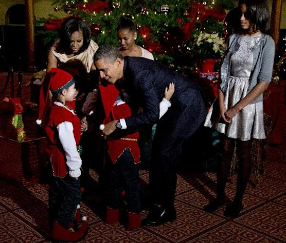 President Barack Obama, center, with, first lady Michelle Obama, back left, and their children Sasha, back center, and Malia, right, greet children dressed like elves at the National Building Museum in Washington, Sunday, Dec. 9, 2012. The first family is attending the taping of the 2012 Christmas in Washington. (AP Photo/Manuel Balce Ceneta)