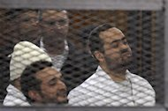 Political activists Ahmed Maher (in white hat), Ahmed Douma (L) and Mohamed Adel (R) of the 6 April movement look on from behind bars in Abdeen court in Cairo, December 22, 2013. REUTERS/Stringer