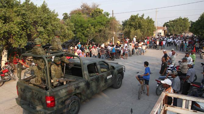 Mexican army soldiers enter the town of La Ruana, Michoacan, Mexico, Monday, May 20, 2013. Residents of western Mexico towns who endured months besieged by a drug cartel are cheering the arrival of hundreds of Mexican army troops. A growing number of people in the state of Michoacan have taken up arms to defend their villages against drug gangs, a vigilante movement born of frustration at extortion, killings and kidnappings in a region wracked by violence. (AP Photo/Marco Ugarte)